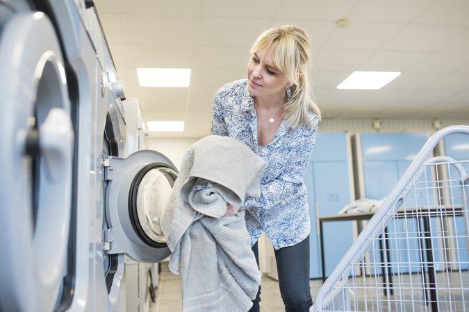 kvinna stoppar i tvätt i torktummlare