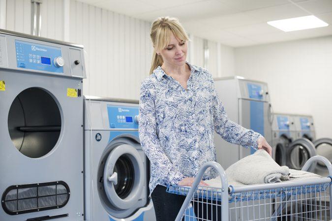 kvinna viker tvätt i tvättstuga