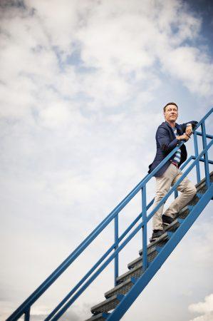 Marcus Brunskog, som är vd för åkeriföretaget Brunskogsgruppen står på en trappa.